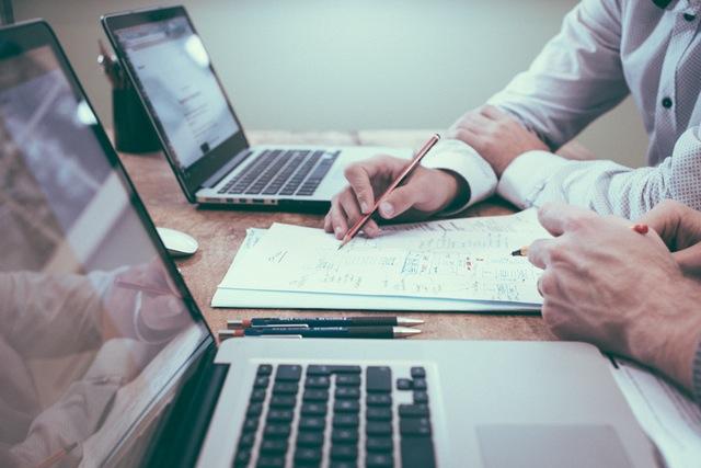 """Foto de pessoas escrevendo em um caderno com dois Macbooks Pro para a pauta """"Como reduzir a inadimplência condominial"""" do Blog da Estasa."""