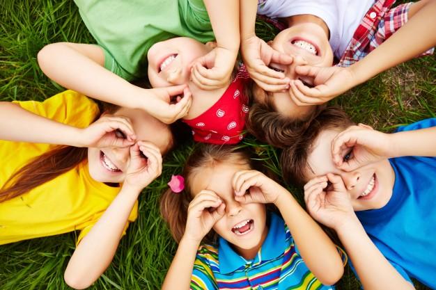 """Foto de crianças brincando na grama para a pauta """"Crianças de férias escolares: cuidados no condomínio"""" do Blog da Estasa."""