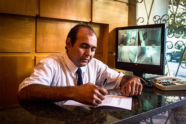 """Foto de um porteiro dentro de uma portaria para a pauta """"Quais as funções de um porteiro de condomínio?"""" para o Blog da Estasa."""
