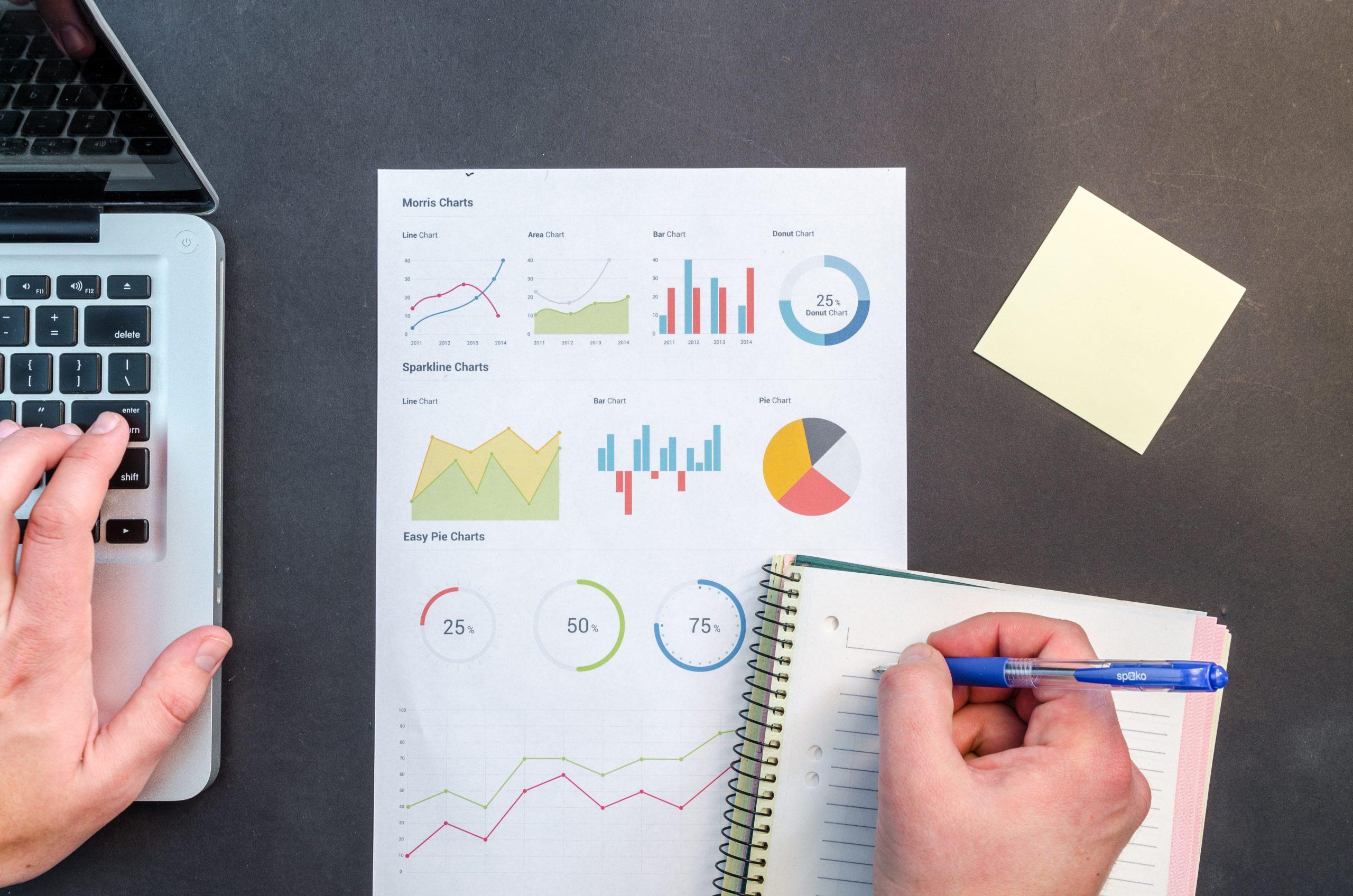"""Foto de uma mão escrevendo dados em um caderno com um relatório com vários gráficos para a pauta """"Despesas ordinárias e extraordinárias: o que são?"""" para o Blog da Estasa"""