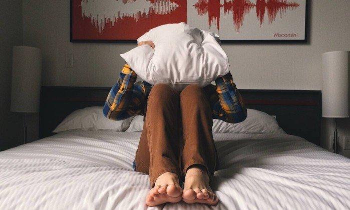 """Foto de uma pessoa sentada em cima de uma cama com um travesseiro na cabeça para a pauta """"Briga entre vizinhos pode acabar em tragédia"""" para o Blog da Estasa."""