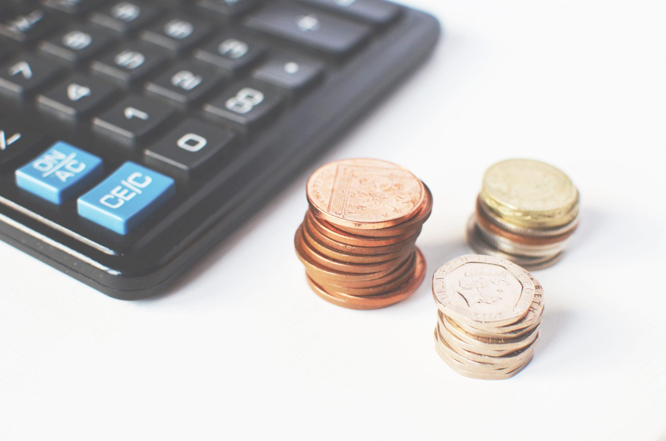"""Foto de uma calculadora e moedas para a pauta """"Como preparar a previsão orçamentária de um condomínio"""" para o Blog da Estasa"""