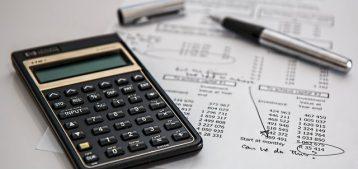 """Foto de uma calculadora e uma prestação de contas para a pauta """"Contas de condomínio - porta para gastos supérfluos e fraudes na administração"""""""