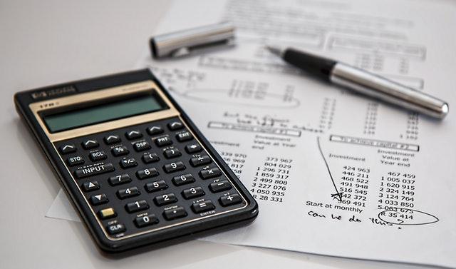 """Foto de uma calculadora e uma folha com vários números para a pauta: """"Entendendo os balancetes de condomínio: o que é o grupo de saldo?"""" para o blog da Estasa"""