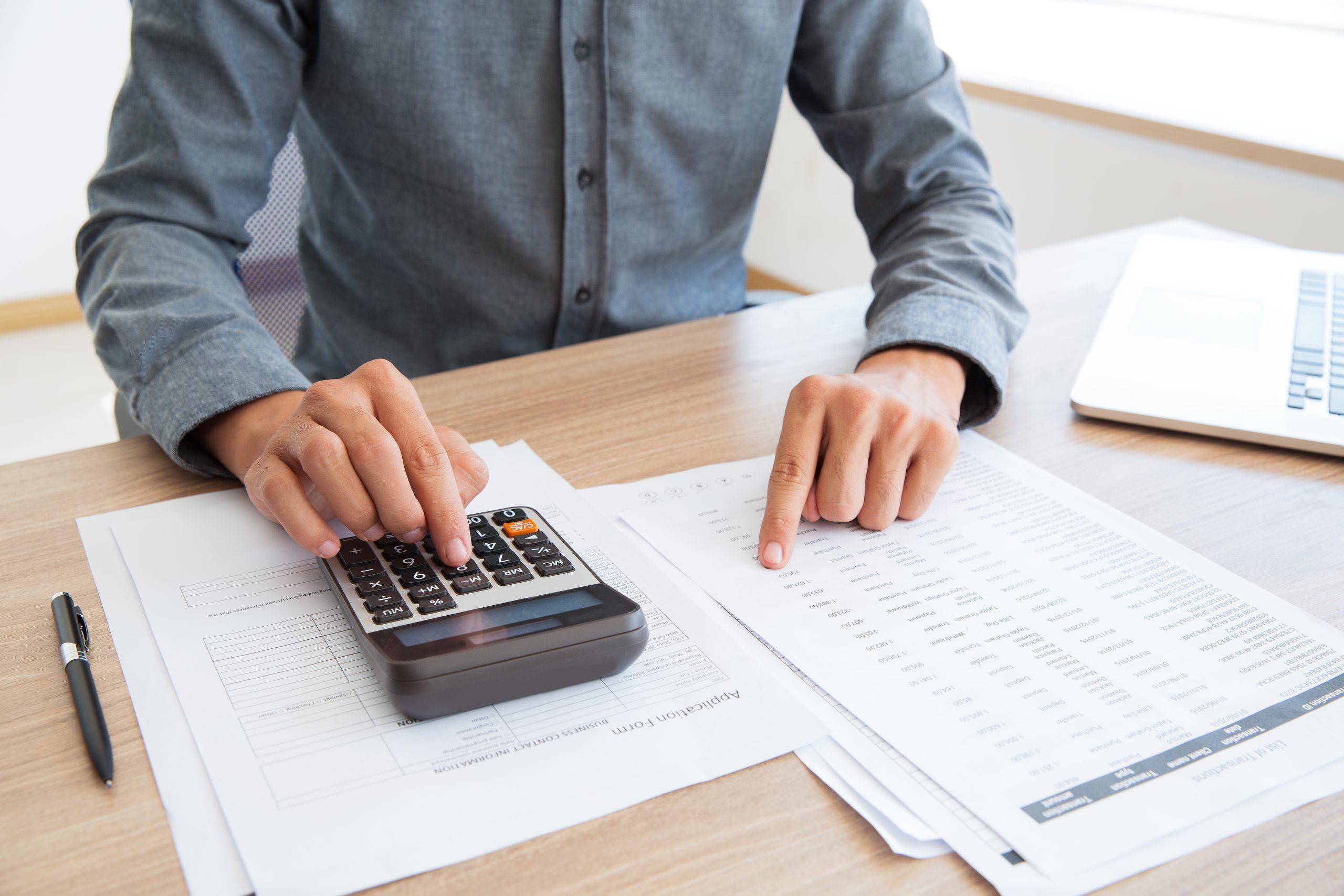 """Foto de uma pessoa mexendo em uma calculadora em cima de uma pilha de papéis para a pauta: """"Contas a pagar, uma das etapas mais complexas da administração condominial"""" para o Blog da Estasa"""